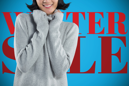 Woman in winter clothing posing against white background against blue background