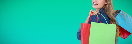 Woman holding shopping bags against abstract green background