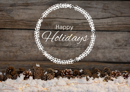 Digital composite of Happy holidays text with wood and pine cones in snow Banco de Imagens