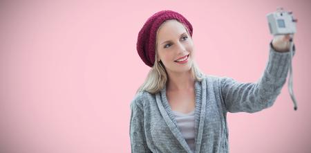 woman taking selfie against pink background