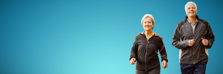 Elderly couple running together against abstract blue background