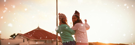 Snow falling against female friends walking on wall during sunset
