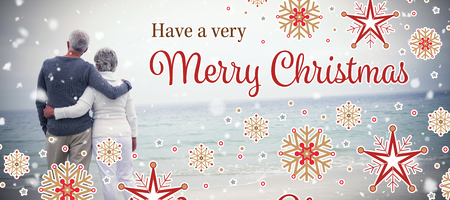 Christmas card against rear view of senior couple embracing at beach