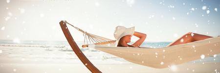 Snow falling against woman wearing sunhat and bikini relaxing on hammock Stock Photo