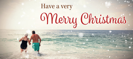 Christmas card against rear view of senior couple holding hands and walking in sea