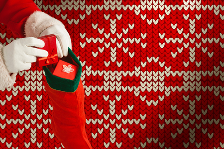 Santa Claus putting presents in Christmas stockings against red seamless knitted pattern Stock Photo