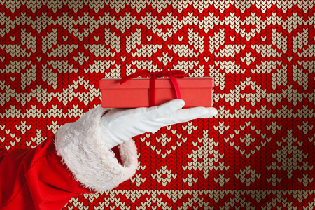 Santa claus holding a gift box in hand against red seamless knitted pattern