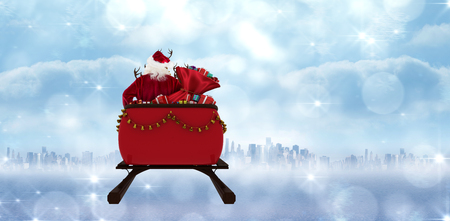 Rear view of Santa Claus riding on sled with gift box against city on the horizon Stock fotó