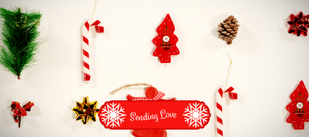 Banner sending love against christmas ornaments against white background