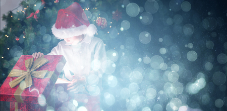 Child opening his christmas present against blue abstract light spot design