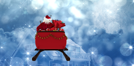 Rear view of Santa Claus riding on sled with gift box against moon lighting house Stock fotó