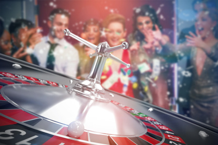 People throwing chips and cash on roulette table against 3D image of ball on roulette wheel
