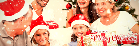 Happy family at christmas swapping gifts against christmas card Stock Photo