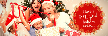 Happy family at christmas opening gifts together against white and red greetings card