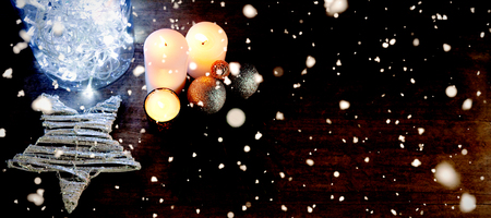 Snow falling against blue lights and yellow candles for christmas