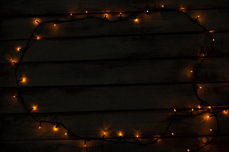 copy space with christmas yellow electric garland on a wooden background