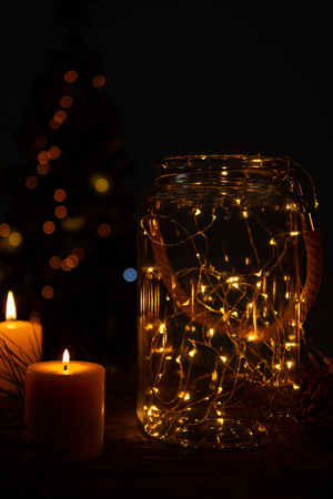 small electric garland in a glass jar with candles and a Christmas tree in the background