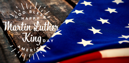 Happy Martin Luther King day, god bless america against folded american flag on wooden table Stock Photo