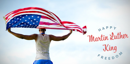 Rear view of sportsman holding american flag  against blue sky with clouds Stock Photo