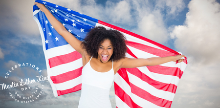 Pretty cheering girl in white top holding american flag against blue sky with white clouds Stock Photo - 111966785