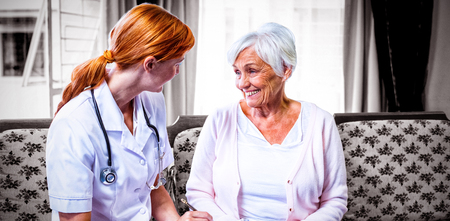 Doctor consulting with senior woman at home Reklamní fotografie