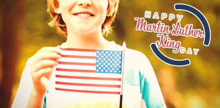 Portrait of cute boy showing American flag against happy martin luther king day Stock Photo
