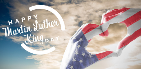 USA flag painted on hands making heart shape against cloudy sky over countryside