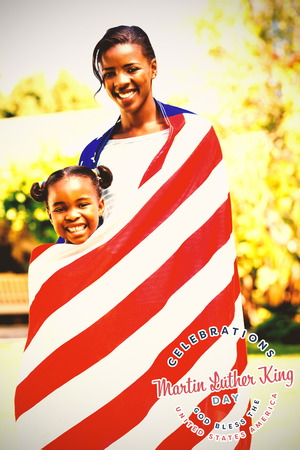 Martin Luther king day against portrait of mother and daughter wrapped in american flag at park Stock Photo