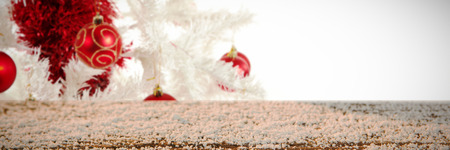 Wooden table covered with snow against red and white christmas decorations Foto de archivo