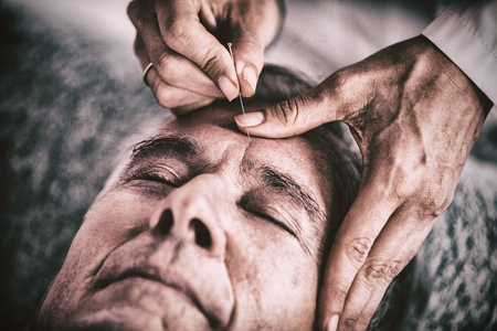 Senior man receiving head massage from physiotherapist in clinic Stock fotó