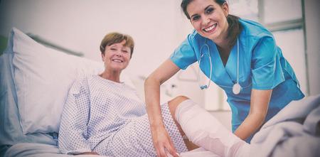 Portrait of smiling nurse bandaging leg of patient in hospital Zdjęcie Seryjne