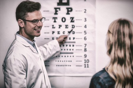 Optometrist taking eye test of female patient in ophthalmology clinic