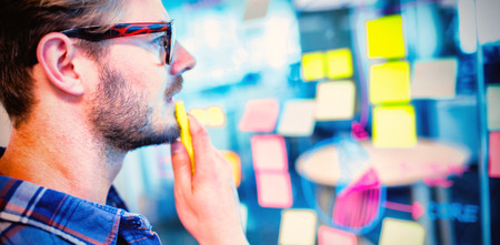 Thoughtful man reading sticky notes on the glass wall in office Imagens