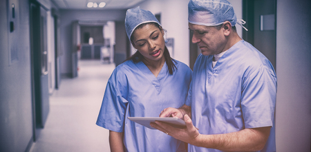 Surgeons discussing over digital tablet in hospital corridor