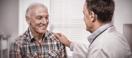 Doctor consoling senior man in clinic