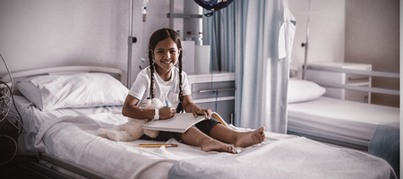 Smiling girl drawing picture in a book while sitting on hospital bed Foto de archivo - 112462264