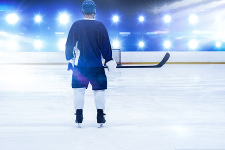 Ice hockey player on the ice against composite image of blue spotlight