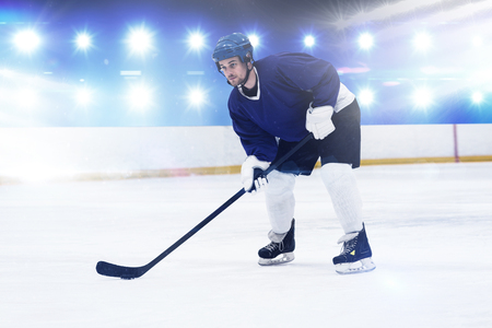 Player playing ice hockey against composite image of blue spotlight Stock Photo