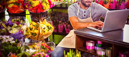 Male florist using laptop while sitting at flower shop