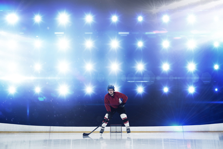 Player playing ice hockey against composite image of blue spotlight 스톡 콘텐츠