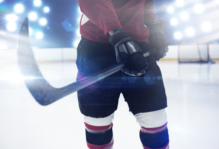 Mid section of hockey player holding stick against composite image of spotlight