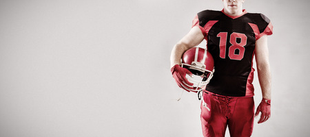 American football player standing with helmet against grey background 免版税图像