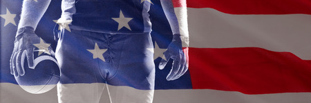 Close-up of US flag against american football player standing with rugby ball