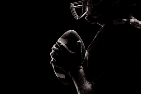 Side view of American football player standing with rugby helmet and ball
