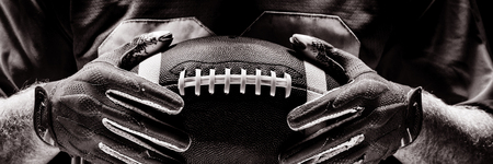 Mid section of American football player standing with rugby helmet and ball Stockfoto