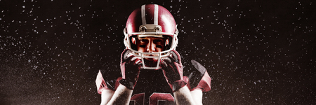 Digitally generated image of powder against american football player standing with rugby helmet