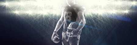 View of spotlights against american football player standing with helmet and rugby ball Standard-Bild