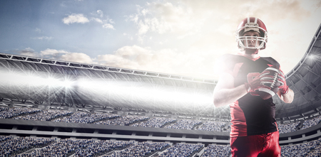 American football player standing with helmet preparing to throw ball against composite image of arena sport against cloudy sky Stock Photo