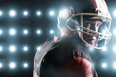 Digitally generated image of blue spotlight  against american football player in helmet standing against black background