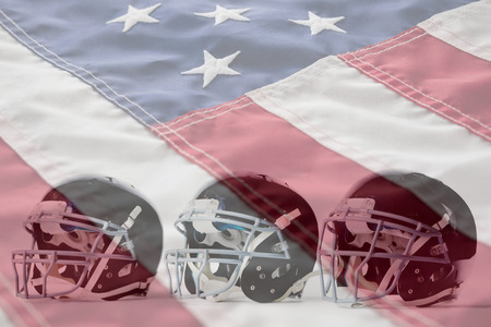 Close up of black sports helmets arranged side by side against close-up of cropped american flag